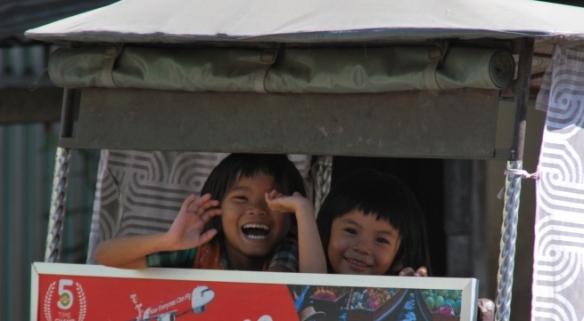 Children wave excitedly from the back of a rickshaw on the streets of Phnom Penh.