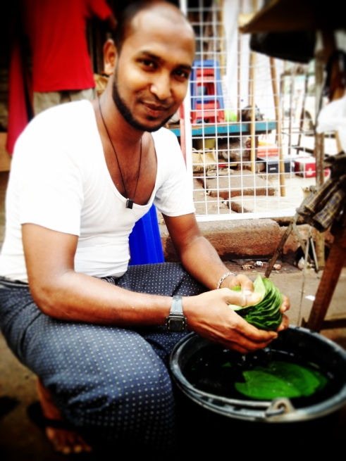 A man washes leaves to wrap betel nuts in, for selling.